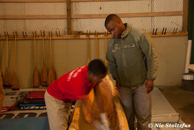 Roy Williams teaching one of the students from the Helena Mighty Quapaw Apprenticeship Program how to carve a dugout canoe.